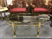 A mid 20th century oval brass coffee table with smoked glass top, 61 cm x 111 cm.