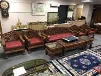 A good quality eight piece carved Eastern hardwood lounge suite, comprising of three seater settee, four single armchairs, coffee table and pair of lamp tables, all profusely carved with flower and vine decoration. (8)