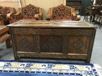 An 18th century oak coffer, with carved frieze, width 126 cm.