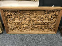 An early 20th century carved Eastern panel, profusely carved with figures in battle, 118 cm x  61 cm.