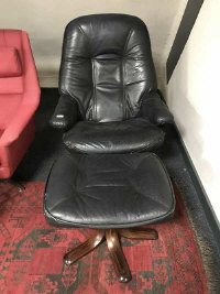 A mid twentieth century Scandinavian black leather relaxer chair with footstool. (2)