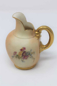 A Royal Worcester blush ivory gilded jug, height 14cm.