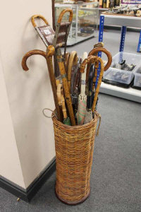 A wicker cylindrical stick stand, containing a quantity of umbrellas, two shooting sticks, walking canes, etc.