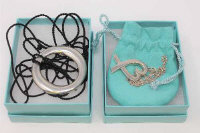 Two Tiffany & Co sterling silver pendants (one on chain), in original retail pouches and both parts boxed. (2)