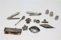 A collection of silver and white metal items including thimbles, combe, military badges, pen knives, contained in a small miniature trunk.