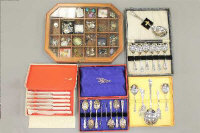 A jewellery display box containing a quantity of costume jewellery, brooches, earrings etc, together with four boxed cutlery sets.