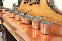 A good set of seven Victorian graduated copper pans with cast iron handles, the largest 53cm in length. (7)