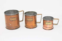 A set of three graduated copper grain measures, the tallest 11cm. (3)