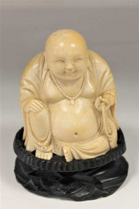 A 19th century Chinese carved ivory figure of a seated Buddha, holding prayer beads, upon a carved hardwood base, height 15cm.