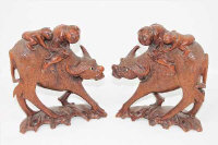 A pair of early 20th century Burmese carved hardwood figures of water buffalo, with riders, height 22cm. (2)