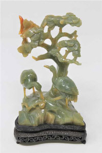 A Chinese jade carving of two cranes beneath a tree, on carved hardwood base, height 21cm.