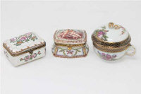 A group of three continental porcelain lidded trinket boxes, one with blue crossed swords mark to base. (3)