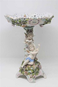 A continental porcelain tazza decorated with cherubs, height 34cm.