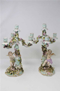 A pair of continental porcelain four-sconce candelabra decorated with cherubs, height 37cm. (2)