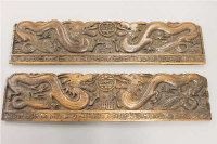 A pair of late 19th century Chinese carved wooden panels depicting dragons, length 91cm.