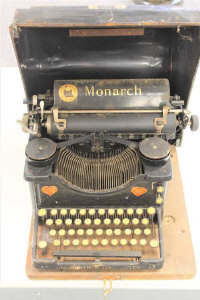 An early 20th century Monarch Visible typewriter in tin case.