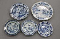 An 18th century tin glazed delft charger, diameter 34.5 cm, together with four further blue and white plates. (5)