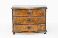 A 19th century burr walnut miniature three drawer chest, width 30 cm, together with a set of draught's pieces.