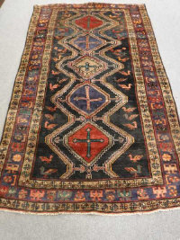 A Persian Lori long rug, with five central medallions upon a black field, 280cm by 160cm.
