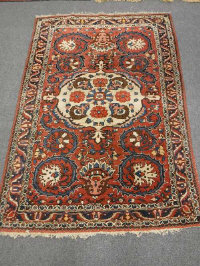 A Bakhtiari rug, West Persia, with a large central medallion upon a strawberry field, 213cm by 140cm.