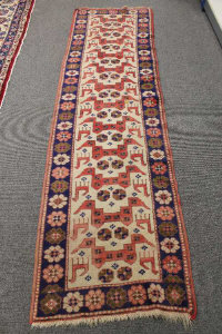 An Anatolian runner, on sand ground with stylized deer enclosed by indigo flower head borders, 245cm by 66cm.