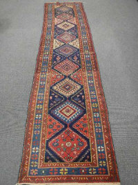A North West Persian runner, late 19th/early 20th century, with nine central medallions upon a midnight blue field, 384cm by 92cm.