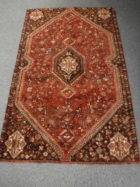 A Kashgai rug, South-West Persia, with a central medallion upon a strawberry field of flower heads and fauna, 209cm by 129cm.