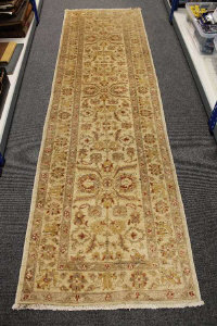 A Persian design runner on sand ground, 294cm by 83cm.