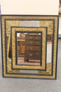 A 19th century ebonised and parcel gilt repousse framed mirror, height 74cm.