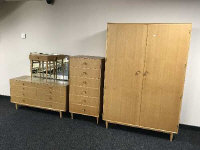 A mid 20th century light oak four piece bedroom suite, comprising of double door wardrobe, six drawer chest, eight drawer mirrored dressing chest and matching bedside cabinet. (4)