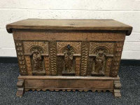 A heavily carved oak blanket chest, with carved detail depicting religious figures, with key, width 90cm.