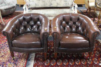 A pair of early 20th century brown Chesterfield style club armchairs, on tapered mahogany legs raised on brass castors, width 77cm. (2)