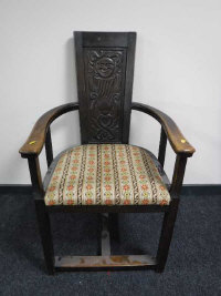 An early 20th century Arts and Crafts style oak armchair with carved panel back, width 62cm.