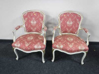 A pair of continental gilded white salon chairs, width 57cm. (2)