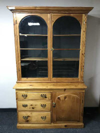 A 19th century pine glazed bookcase fitted with three drawers and a cupboard below, width 131cm.