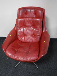 A mid 20th century red leather swivel relaxer chair, width 77cm.