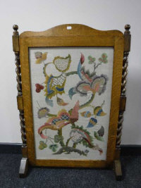 An Edwardian oak fire screen with embroidered panel, width 64cm.