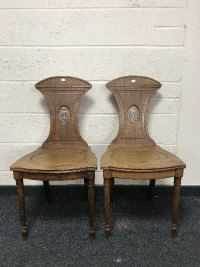 A pair of 19th century mahogany hall chairs with crested backrests, width 46cm. (2)