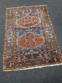 A Kazak rug, with two geometric medallions upon a blue field, enclosed by borders of flower heads and angular vines, 193cm by 141cm.