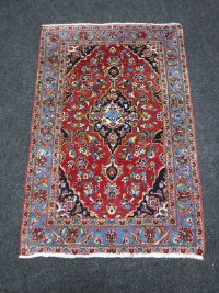 A Kashan rug, a central strawberry medallion enclosed by blue scrolling vine borders, 148cm by 98cm.