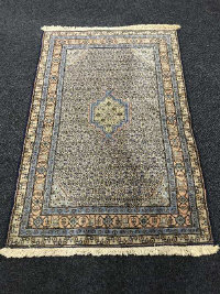 A fringed Persian rug on blue ground, 173cm by 114cm.