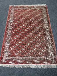 A fringed Afghan rug on red ground, of geometric design, 200cm by 135cm.