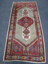 A North-West Persian village rug, 244cm by 109cm.