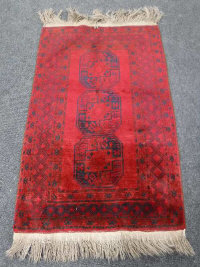 A fringed Afghan Bokhara rug, on red ground, 178cm by 101cm.