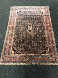 A Persian rug, on pink and indigo ground, 201cm by 136cm.