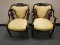 A pair of carved mahogany armchairs in gold upholstery, width 60cm.