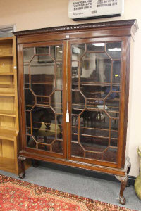 A late Victorian astral glazed mahogany display cabinet, on claw and ball feet, width 134cm.