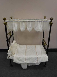 A Victorian cast iron and brass doll's canopy bed, length 89cm.