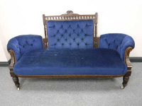 A Victorian oak button-back settee, on carved legs terminating in ceramic castors, width 186cm.