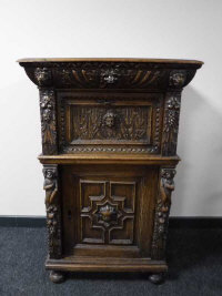 A 19th century carved oak cabinet, fitted two cupboards and a drawer, width 71cm.